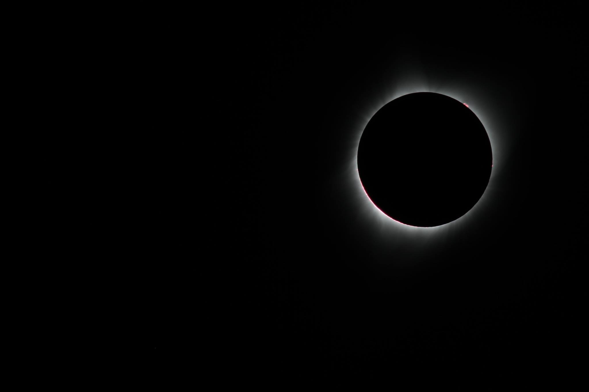 an image of a total solar eclipse, with a red flare in the upper right corner, and light shining all around in a ring